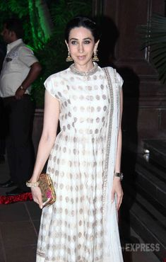 karishma kapoor in white gold dress she look elegant in a gold and beige Anita Dongre suit with jhumkis and Princesse K clutch.