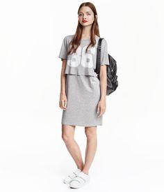 Kurzes Kleid aus weichem glänzendem Jersey. Das Kleid hat ein doppellagiges Oberteil und Kurzarm.