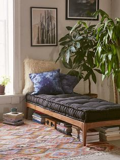 Use a daybed to break up those large complicated spaces. When homes or apartments have long and narrow living rooms or combine the living and dining areas, it can be a challenge to center each living space appropriately. Try squeezing a day bed in between, with plants on one side, as seen in this Urban Outfitters example.