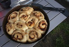 Cinnamon rolls baked on a campfire in iron skillet.