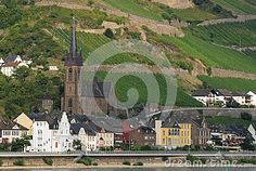 Photo made at a small town in the Rhine Valley in Germany. In the picture you see, across the river, the large dark-colored church surrounded by houses almost all white. The ahill is located at the back of the town is completely covered with vineyards by green vineyards.