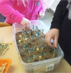 Marble Balance Game ....  Fine motor skill activity using a tub of sand, golf tees and marbles.  Children stick golf tees into sand and try to balance marbles onto top of the tees.