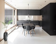 A family of Eames Molded Plastic Side Chairs surround a Loop Stand High Table by HAY in the dining area. Aplomb suspension lamps by Foscarini, a Smeg stove, and an oblong Cut vase by Studio Minotti for Bosa adhere to the home's black and white color palette.