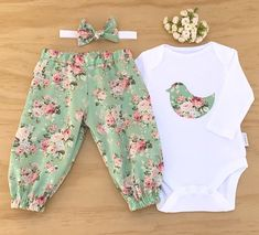 Little girls matching bodysuit, harem pants and headband. The bodysuit is appliqued with a very sweet Dove in a green and pink rose fabric that has been heat bonded to the bodysuit then machined stitched around the edge. The applique is designed to fray slightly when laundered.
