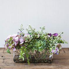 Centro de mesa rectangular con hortensias y rosas de seda en tonos morados y lilas combinado