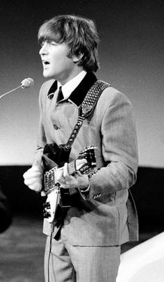 """Photo of John Lennon performing with the Beatles in 1964. Credit: VARA; Wikimedia Commons. Read more on the GenealogyBank blog: """"34th Anniversary of Ex-Beatle John Lennon's Death."""" http://blog.genealogybank.com/34th-anniversary-of-ex-beatle-john-lennons-death.html"""
