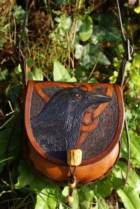 crow with triple knot design on a rich brown leather bag with additional carving on the back