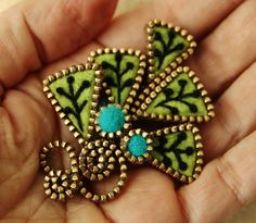 """Felt """" Ginkgo leaf """" inspired brooch enveloped with pieces of brass zipper.The leaves have been embellished with hand embroidery .I have used a beautiful shade of lime green 100 %Merino felt to make this brooch.I further embellished the brooch with two turquoise green felt beads enveloped with pieces of brass zipper.The approx dimensions of the brooch are 2"""" x 2 1/2""""."""