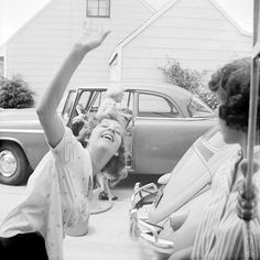 Bratty teenage girl standing in driveway behind late 1950s Volkswagen Beetle goofs next door grandma as old grouch unloads groceries from back seat of plain Jane 1955 Plymouth Plaza. 1950s 1960s vernacular photo snapshot--http://reservatory.net