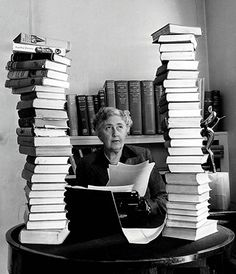Agatha Christie behind her desk with towers of her own books piled around her.