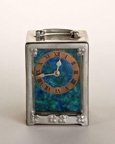 Carriage clock, c. 1901 Tudric line, Pewter, enamel, Designer: Archibald Knox, 1864-1933, Birmingham, England Maker: W. H. Haseler and Co., 1870-c.1926, Birmingham, England Retailer: Liberty & Company, 1875-present, London Marks
