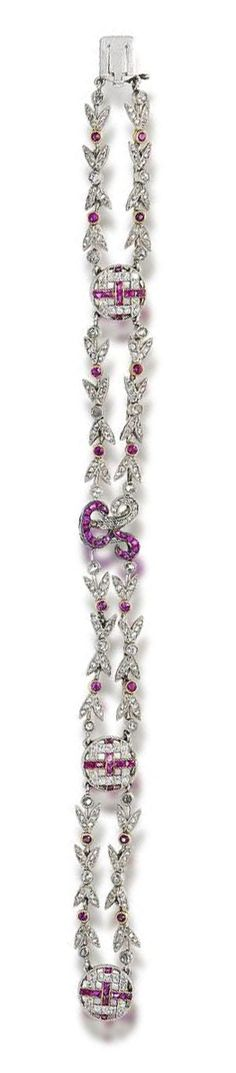 A belle époque ruby and diamond bracelet, circa 1905  The double row of foliate links, interspersed with pierced circular spacers and a scrolling letter R at the centre, set throughout with circular and calibré-cut rubies and cushion-shaped and rose-cut diamonds, all within millegrain settings, length 19.0cm, fitted case by Carrington & Co Ltd, 130 Regent Street, W.1.