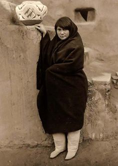 You are looking at an educational picture of a Zuni Maiden. It was taken in 1903 by Edward S. Curtis.    The picture presents a Zuni woman in a full-length portrait, standing, facing front, wearing a blanket.    We have created this collection of pictures primarily to serve as an easy to access educational tool. Contact curator@old-picture.com.    Image ID# A9D30E2E