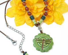 """By """"pretty Gonzo"""" on Etsy: This boho statement necklace features a bold green dragonfly pendant, Mykonos ceramic beads, carnelian gemstone rounds, and shiny pewter beads. Dragonfly Necklace, Dragonfly Pendant, Beaded Dragonfly, Leather Necklace, Boho Necklace, Necklaces, Pendant Necklace, Bracelets, Handmade Jewelry"""