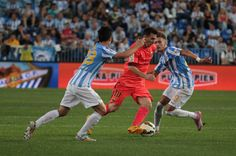Lionel Messi of F.C. Barcelona (C), duels for the ball with Juan Pablo Anor alias Juanpi (L) and Samuel Castillejo (R) of Malaga CF during the La Liga match between Malaga CF and FC Barcelona at La Rosaleda studium on September 24, 2014 in Malaga, Spain.
