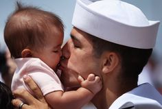 <b>Military men returning home from deployment have their first moments with their newborn sons and daughters.</b>