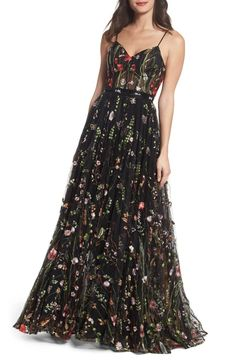 A lush garden of embroidered flowers enlivens a subtly sultry gown topped with a bustier-style bodice that flows into a billowy skirt.