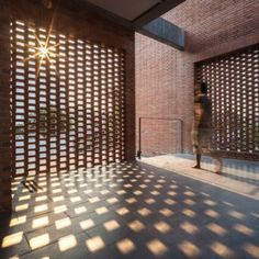Brick grates set into the walls of a Bangkok house hide a series of outdoor spaces