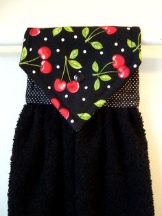 Hanging hand towel with red cherries scattered on a black background, and a black terry cloth towel. Lining is black with white pin dots.
