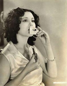 silent film actress Raquel Torres  using a lip stencil