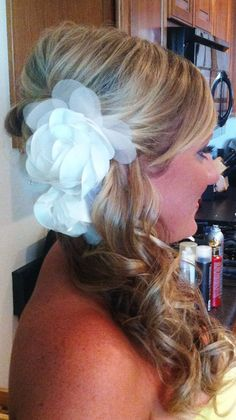 Perfect for a summer wedding! This bridal updo features a teased side ponytail, long beachy waves and a big, fun flower to accessorize. Run your fingers through your curls to loosen them up for a more laid back look.