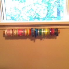 Ribbon holder made from wrapping paper tube and eye hooks for hanging.