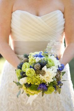 {Bride's Lovely Round Bouquet Made Up Of Blue Delphinium, Blue Eryngium Thistle, Ivory Roses, Ivory Chrysanthemums, Green Roses, Green Trick Dianthus, Green Viburnum, & Scabiosa Pods}