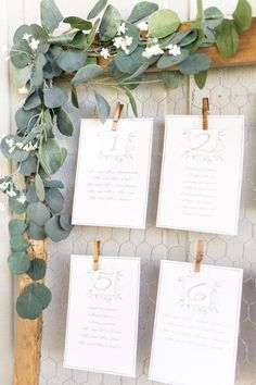 Rustic wire clipped wedding escort card display with cascading eucalyptus: http://www.stylemepretty.com/florida-weddings/malabar-florida/2017/02/28/we-should-all-follow-this-brides-simple-wedding-planning-advice/ Photography: Amalie Orrange - http://amalieorrangephotography.com/ #weddingdecoration
