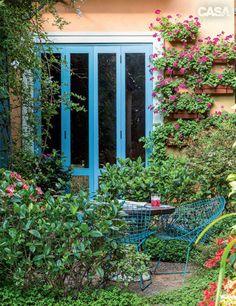 A gardênia (Gardenia jasminoides) envolve o recanto de mesa e cadeiras, enquanto gerânios (Pelargonium peltatum) pendem de jardineiras nas paredes.