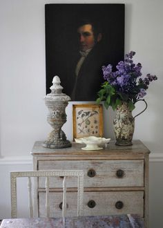 Diminutive Swedish Chest under an American Portrait with a splash of purple.
