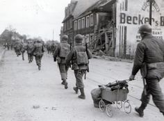 Soldier carrying mortar in baby carriage in Saarbrucken as troops moved into the city today, 20 March 1945. 274th Infantry Regiment, 70th Division. Photo: National Archives.