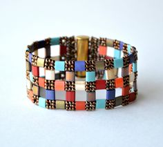 A beautiful medley of Tila beads were used to create this 'Patchwork Florentiles' Cuff. Beaded by Debra using Diamond Weave. Inspired by 'Florentiles' Necklace design by Gerlinde Lenz.