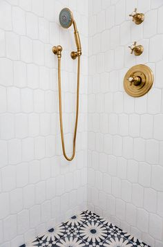 Brass Shower Faucet. Brass Shower Faucet Ideas. Brass Shower Faucet against white tiles and cement floor tiles. The shower brass faucets are from Newport Brass and the finish is Forever Brass. #BrassShowerFaucet