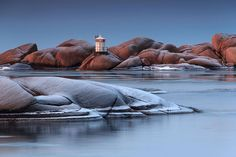 Stangholmen in Lysekil, Sweden   This lighthouse appears smaller than others, uniquely stacked atop these smooth-surface rocks. It is one of many lighthouses found throughout Sweden.