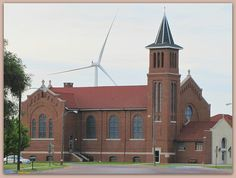 St. John Catholic Church in Spearville, Kansas has one of the huge  windmills looming over it