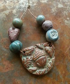 Forest of Dreams… This hand formed ceramic acorn and leaf pendant and bead set is glazed in sweet greens, purples and blues by Gaea Cannaday.