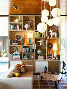 Cool big block shelves. More of a display unit, fun accessories over book storage. Love the hanging lamps as well.