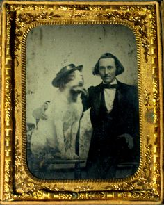 ca. 1850-60's, [ambrotype portrait of a smirking gentleman with his dog, wearing a hat and chewing on a glove]