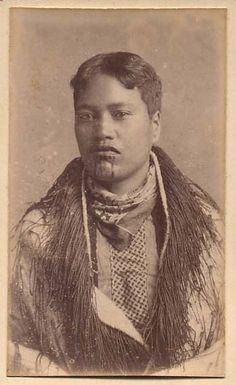 Young Maori woman with chin moko, wearing a korowai cloak and western-neckerchief,1880s.