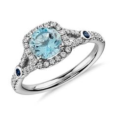 Aquamarine and Diamond Split Shank Halo Ring in White Gold A vision of color, this gemstone ring features a round aquamarine surrounded by a halo of round brilliant diamonds, and accented with two vibrant blue sapphires framed in white gold. Blue Nile Jewelry, Aquamarine Jewelry, Birthstone Jewelry, Gemstone Jewelry, Ring Ring, Blue Rings, White Gold Rings, Pretty Rings, Beautiful Rings