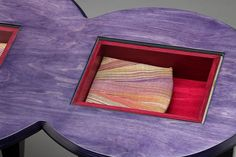 Figure Eight Table by Anne Bossert. This purple handmade table is made of dyed Baltic birch plywood and features hand dyed handwoven cotton fabric that is pieced and sewn together in semi-circles. The two fabric semi-circles are each housed in boxes that drop below the surface of the table top and are protected under glass that sits flush with the top. The laminations of the plywood are used throughout the piece as decorative striped elements as seen in finger joints on the boxes and…