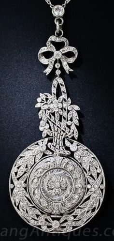 An Edwardian platinum and diamond pendant watch. The pendant watch framed and swings freely within a diamond-set wreath, the watch and wreath transition into a delicate, asymmetrical basket of flowers, held by a bow knot. #Edwardian #PendantWatch