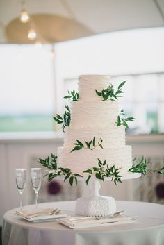 White Wedding Cake with Fresh Greenery | Sean Money + Elizabeth Fay Photography on @acoastalbride