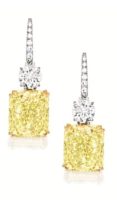 PAIR OF FANCY INTENSE YELLOW DIAMOND AND DIAMOND PENDENT EARRINGS Each set with a cut-cornered rectangular modified brilliant-cut diamond weighing 7.73 and 7.54 carats respectively, each surmounted by a brilliant-cut diamond weighing 0.91 carat, mounted in platinum and 18 karat yellow gold.