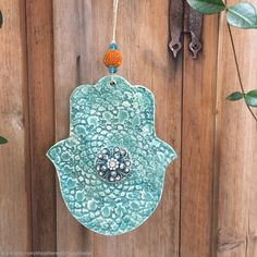 I formed this hamsa using high-fire white earthenware clay, in hand-built method. Using my various stamps and tools, I cut and textured this hamsa shape, then fired it to bisque. After taking it out of the kiln, I glazed it with lead-free turquoise  glaze and high fired it again in my kiln at my studio.  I added a beautiful silver-look flower pendant to the center of the hamsa, finishing it with orange and turquoise glass beads. Ceramic hamsas by KerenOrHandmade on Etsy