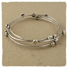 """These three wispy bangles are speckled with dots of silver and settle about the wrist in a never ending variation of patterns. Hand oxidized and finished to a shiny patina.  Available in 8"""", 8 1/2"""", or 9"""""""