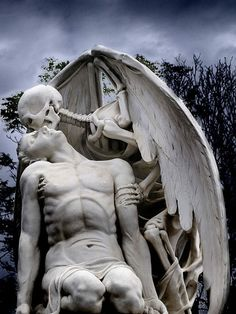 """The Kiss of Death Statue in the Old Graveyard of Poblenou, Barcelona Spain.  The tomb's inscription: """"His young heart is thus extinguished. The blood in his veins grows cold. And all strength has gone. Faith has been extolled by his fall into the arms of death. Amen."""""""