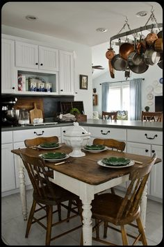 Cute cottage and I love the table and chairs and dishes! Also ... copper pots!