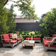 Soften the space between a patio and privacy fence with plants like hydrangeas that freely flow. And add a pop of color with bright red cushions - who wouldn't love this summer look at their house?!