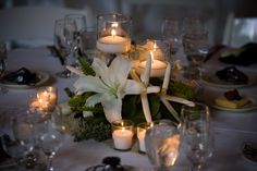Using a tailored palette of white and green with accents of black, shells and white starfish were incorporated throughout the decor as a unifying element. This is an elegant and tailored look to complement any kind of ceremony decor. The centerpieces, designed in a low dish surrounded by beach sand and shells, had white Casablanca lilies, moss and succulents along with floating candles and votives.
